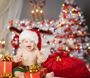 Christmas Baby in Santa Hat, Kids Xmas Present Gift. Christmas Baby in Santa Hat, Kid Boy in Xmas Interior, Present Gift Box and Bag royalty free stock images
