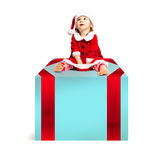 Christmas Baby in Santa Hat sitting on Big Xmas Gift Box Stock Photo
