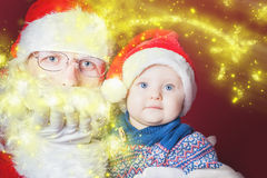 Christmas baby and Santa opening a present or gift box Royalty Free Stock Photography