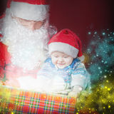 Christmas baby and Santa opening a present or gift box Royalty Free Stock Photos