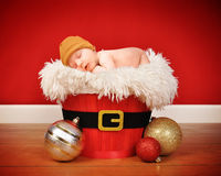 Christmas Baby Sleeping in Santa Basket. A cute little baby is sleeping in a santa wooden basket with a red background for a portrait or christmas concept royalty free stock image