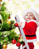 Christmas baby on a step ladder. Happy Christmas baby standing on a step ladder decorating Xmas tree Stock Image