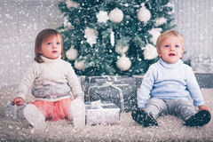Christmas baby twins. Cute baby twins boy and girl with christmas tree and gift Stock Photos