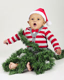 Christmas Baby Wrapped in Garland Stock Photography