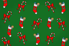 Christmas background. A background pattern featuring randomly placed Christmas socks and sticks on green background Royalty Free Stock Photography