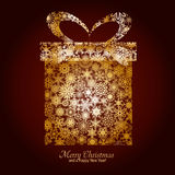 Christmas background 8. Christmas card with gift box made from gold snowflakes on brown background and a wish of Merry Christmas and a Happy New Year Stock Image