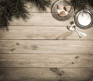 Christmas background. Antique wooden table, pine branch and vintage items. Silver tray, fork and spoon, tied with a pink bow. Copy royalty free stock images