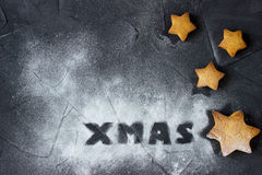 Christmas background with baked gingerbread stars and word Xmas made from powdered sugar. creative idea. Christmas background with baked gingerbread stars and Stock Photography