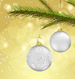 Christmas background with ball decorations. Two silver christmas ball decorations hanging on the barach of the pine tree Royalty Free Stock Images