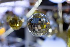Silver christmas disco ball on a blurred festive background in time for new year holiday. Christmas background with a ball on a tree royalty free stock image
