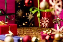 Christmas Background with Baubles, Bows and Boxes. Christmas gifts, glitter balls and straw stars on a festive cloth. Seasonal background with focus on the Royalty Free Stock Photo