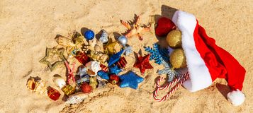 Christmas background on the beach with shells on the sand royalty free stock photos
