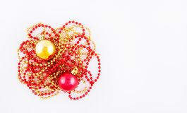 Christmas background with beads and Christmas balls. Red and gold christmas-tree decorations on white background. Royalty Free Stock Photos