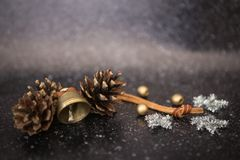 Christmas background black with a metal bell and two pines, silver sparkling Snowflakes stars and gold balls Royalty Free Stock Photos