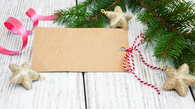 Christmas background - blank paper with decoration. Christmas background - blank paper card, stars  and fir branch on a wooden table Royalty Free Stock Photo