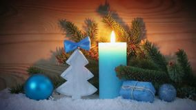 Advent candle and blue decoration with snow. Christmas background. Christmas background with blue Advent candle ,fir tree and white snow stock video