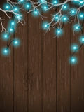 Christmas background, blue lights on dark wood, illustration. Christmas background, blue electric lights on dark wooden wall hanging in white dry branches Stock Photo