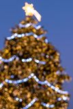 Christmas background - blurry lights decoration on large Christmas. Tree against twilight sky stock photography