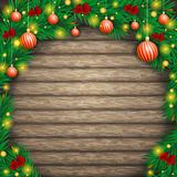 Christmas background of boards in an arch  fir branches. Christmas background of boards in an arch of fir branches, decorated with ribbons, balls and lanterns Stock Photo