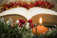 Christmas background with book and candle. Red decorations with open book and lit candle Stock Photography