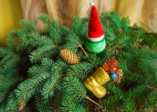 Christmas background, boots with gifts, Xmas balls on spruce branches and cap Stock Photos