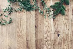 Christmas background. Border, frame of green fir, eucalyptus and pine tree branches on old wooden oak table. Winter. Festive banner. Vintage look, flat lay, top stock image