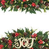 Christmas Background Border. With gold joy sign, holly, ivy, mistletoe, fir and pine cones on white Stock Photos