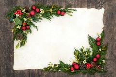 Christmas Background Border. On parchment paper on oak wood with red bauble decorations, holly, mistletoe, ivy, fir and pine cones royalty free stock photos