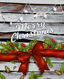 Christmas background with bow ,fir branches and red berries on w. Ood Stock Photo