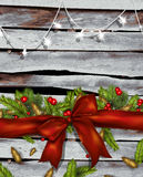 Christmas background with bow ,fir branches and red berries. On wood Royalty Free Stock Photo