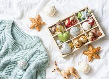 Christmas background. Box of vintage christmas decorations and blue knitted sweater on the bed, view from above. Christmas cozy mo. Od still life Royalty Free Stock Photo