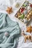 Christmas background. Box of vintage christmas decorations and blue knitted sweater on the bed, view from above. Christmas cozy mo. Od still life Royalty Free Stock Photos