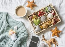 Christmas background. Box of vintage christmas decorations, coffee with milk, phone and blue knitted sweater on the bed, view from. Above. Christmas cozy mood royalty free stock photo