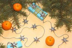 Christmas and New Year`s gifts in blue boxes lie under a Christmas tree next to tangerines and silvery stars. Royalty Free Stock Images