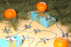 Christmas and New Year`s gifts in blue boxes lie under a Christmas tree next to tangerines and silvery stars. Stock Photos
