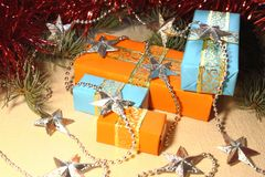 Gifts for the holiday Christmas and New Year in orange and blue boxes lie under a Christmas tree next to tinsel and silvery stars. Stock Images