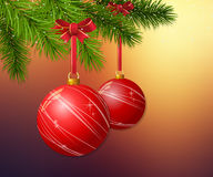 Christmas background with branch and Christmas balls. Christmas balls with bows hanging on branch on blurry sunset background Stock Photography