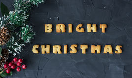 Christmas background with branch of christmas tree and baked gingerbread words bright christmas . creative idea Stock Images