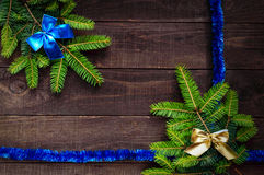 Christmas background. Branch spruce decorated with bright ribbon on a dark wooden background. Royalty Free Stock Image