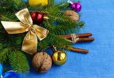 Christmas background. Branch spruce decorated with colorful decorations, nuts and cinnamon Stock Photography
