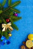 Christmas background. Branch spruce decorated with colorful decorations, nuts, cinnamon, lemon on blue napkin. Royalty Free Stock Photography