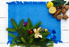 Christmas background. Branch spruce decorated with colorful decorations, nuts, cinnamon, lemon on blue napkin Royalty Free Stock Photo