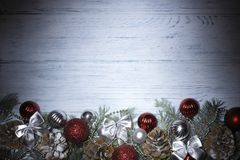 Christmas 2020 background. Branches of a Christmas tree, pine cones, red balls, bows, ribbons on a wooden texture. Christmas 2020 background with branches of a royalty free stock photo