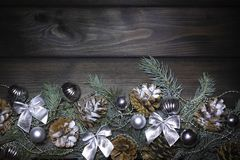 Christmas 2020 background. Branches of a Christmas tree, pine cones, silver balls, bows, ribbons on a wooden texture. Christmas 2020 background with branches of stock image