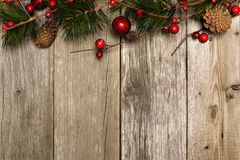 Christmas background of branches on wood. Aged wood Christmas background with branches and baubles top border Royalty Free Stock Photography