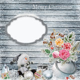 Christmas background with a bunch of flowers with frost, snowman, frame for text or photos, Christmas decorations on a snowy woode Stock Photos