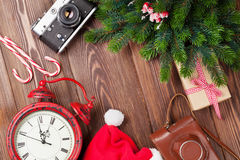 Christmas background with camera, alarm clock and tree branch Stock Images