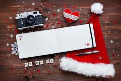 Christmas background with camera, hat, notepad and Ho-Ho-Ho. Royalty Free Stock Image