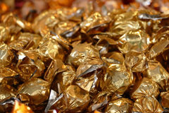 Christmas background, candies wrapped in golden metal foil. Candies wrapped in golden metal foil, glittering background for christmas, new year or easter royalty free stock image