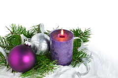 Christmas background with candle and decorations. Purple and silver Christmas balls over fir tree branches Stock Photos